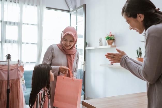 小さなブティックショップで買い物をする魅力的なアジアのイスラム教徒の母と娘