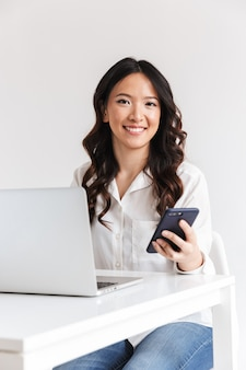 Attractive asian office woman with long dark hair sitting at table and holding smartphone while working with laptop