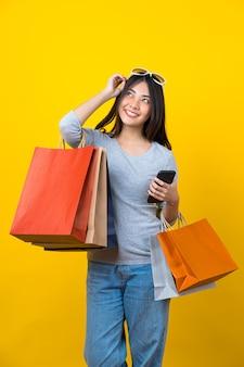 Привлекательная азиатская улыбающаяся молодая женщина, несущая мобильный телефон с цветной сумкой для покупок