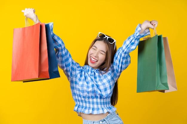 Привлекательная азиатская улыбающаяся молодая женщина, несущая красочную сумку для покупок на изолированном желтом цвете