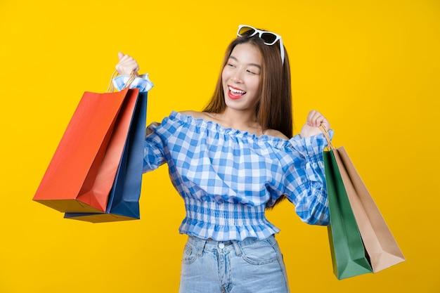 Привлекательная азиатская улыбающаяся молодая женщина, несущая сумку для покупок на изолированные