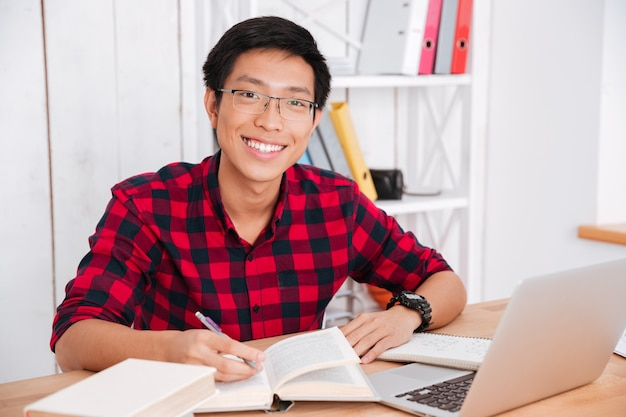 Attractive asian student looking at front and writing notes while reading a books and working on laptop in classroom