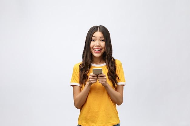 Привлекательная азиатская девочка-подросток, глядя на экран своего мобильного телефона
