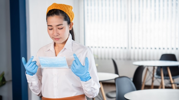 Attractive asian waitress wear face mask to protection epidemic virus outbreak