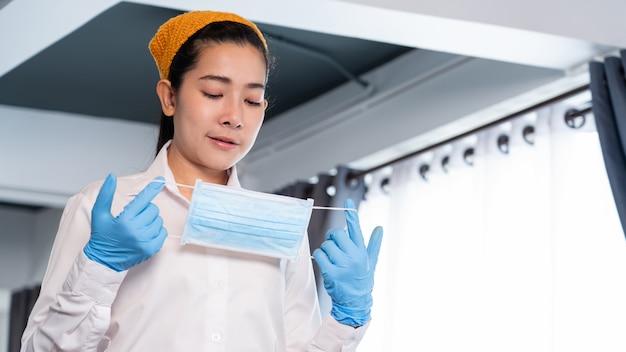 매력적인 아시아 웨이트리스는 전염병 바이러스 발생을 보호하기 위해 얼굴 마스크를 착용