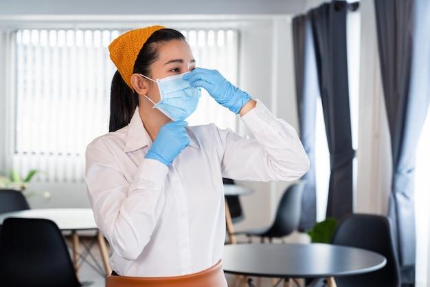 魅力的なアジアのウェイトレスは、流行のウイルスの発生を保護するためにフェイスマスクを着用します
