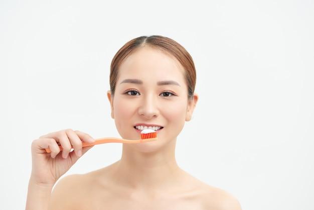 Привлекательная азиатская женщина, чистящая зубы на белой стене