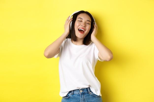魅力的なアジアの女性は、ワイヤレスヘッドフォンで音楽を聴き、満足して笑って、一緒に歌って、黄色の背景を楽しんでいます。