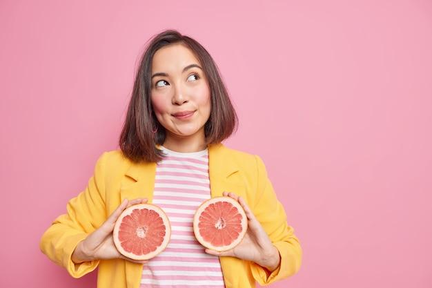 매력적인 아시아 여자 사려 깊은 꿈꾸는 표현 보유 자몽 반쪽은 육즙 감귤류 과일을 먹고 칼로리를 태우고 건강한 영양이 복사 공간 영역이있는 분홍색 벽에 포즈를 취합니다.