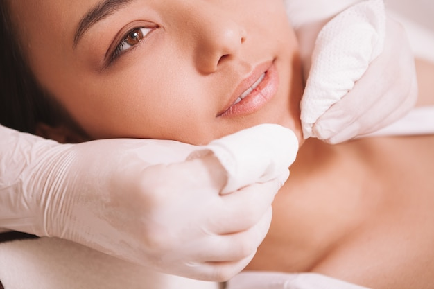 Attractive asian woman having pimples and blackheads removed by cosmetologist