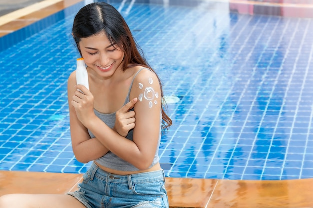 Attractive asian woman holding a bottle of sunblock and applying sun shaped sunscreen uv protect to shoulder.