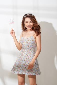 Привлекательная азиатская женщина в цветочном платье с леденцом в руке