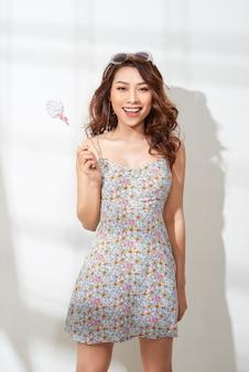 手にロリポップと花のドレスで魅力的なアジアの女性