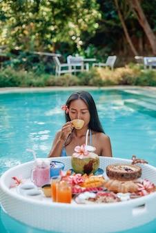 さまざまなエキゾチックな食べ物で満たされたフローティングテーブルとスイミングプールの魅力的なアジアの女性は、フルーツジュースを飲みます。