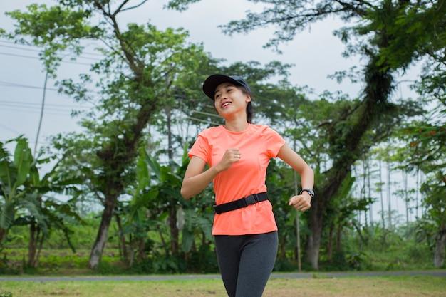 公園でジョギングする魅力的なアジアの女性