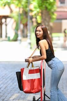 외부 장벽에 기대어 복고풍 카메라 쇼핑백을 가진 매력적인 아시아 여성 모델