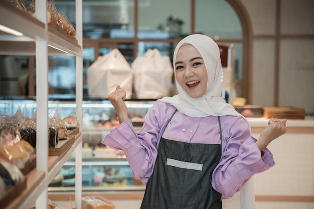 魅力的なアジアの女性は、店主として彼女の店で働いている間、彼女の腕を上げます。パン屋のイスラム教徒の事業主