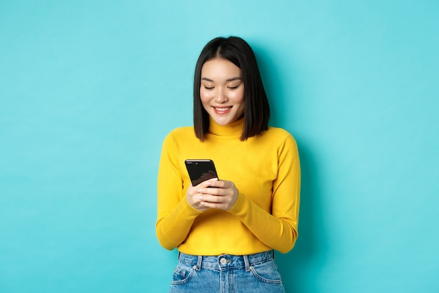 Attractive asian woman reading smartphone screen and smiling, social networking with mobile phone, standing over blue.