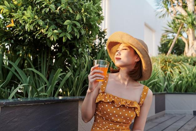 公園でリラックスして飲む魅力的なアジアの女性