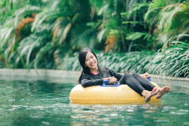 Attractive asian woman relaxing at river pool