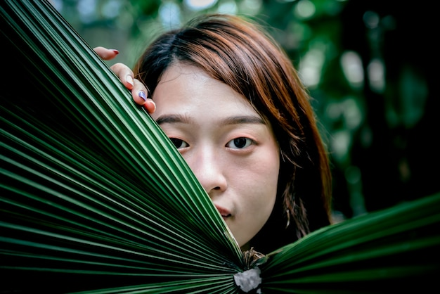 Attractive asian woman's face, hiding behind green palm leaves