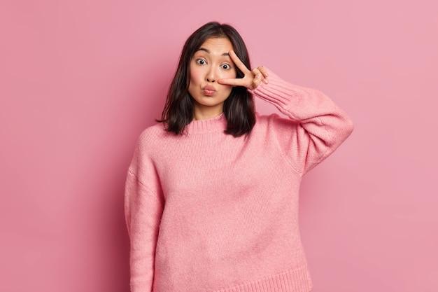 魅力的なアジアの女性は目の上の勝利のサインを示し、唇を丸く保ち、ディスコのジェスチャーを楽しんで屋内でカジュアルなセーターを着ます