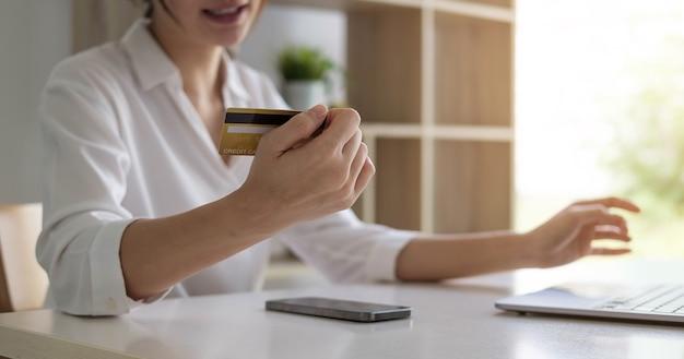 Привлекательная азиатская женщина расслабленно сидит на диване, держа в руке кредитную карту и смартфон, вероятно, покупая что-то в интернете.