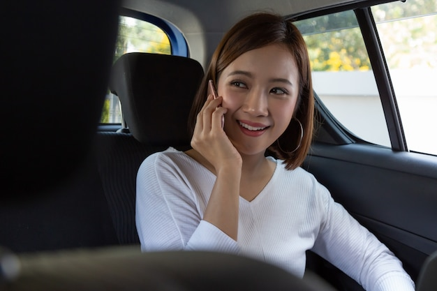 Attractive asian woman talking on the phone while traveling and sitting in the back seat of the car