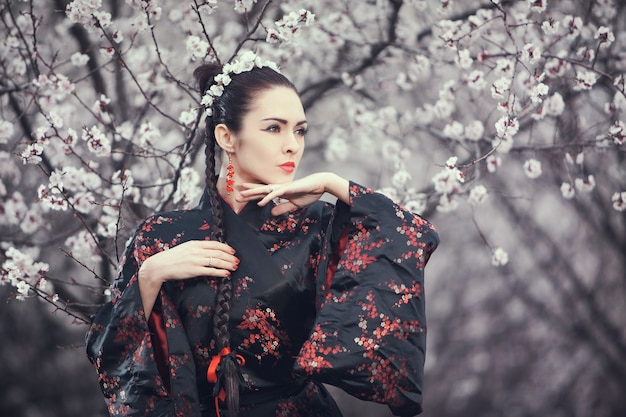 花の咲く庭に立っている着物を着ている魅力的なアジアの女性。