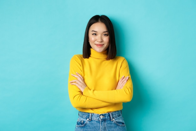 Привлекательная азиатская женщина с короткими темными волосами, скрестив руки на груди и уверенно улыбаясь, стоя на синем фоне.