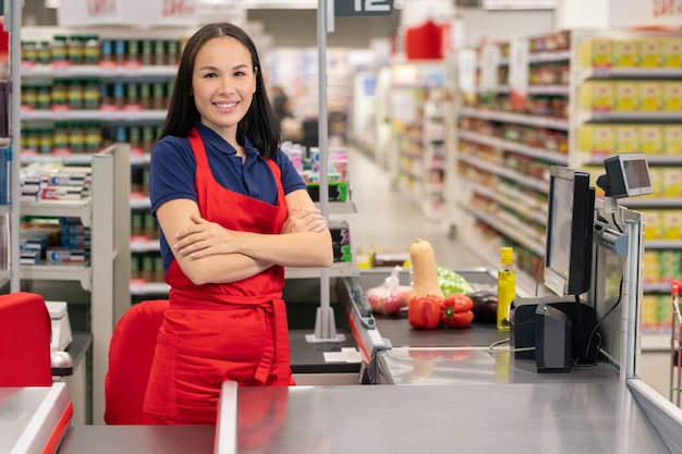 Attractive asian woman working in supermarket standing at cash desk with arms crossed
