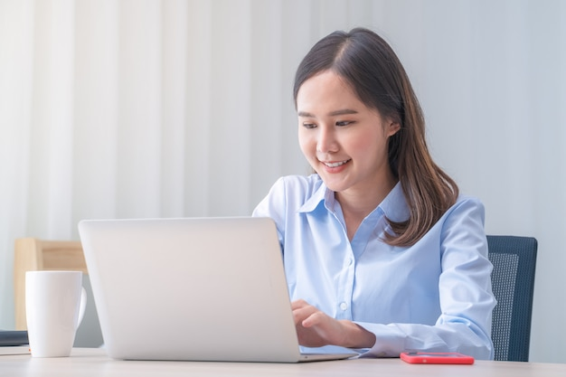 Attractive asian woman works from home with laptop on desk in bedroom. young girl smiling with happiness face while reading at computer screen. telecomuting, freelancer and modern lifestyle concept.