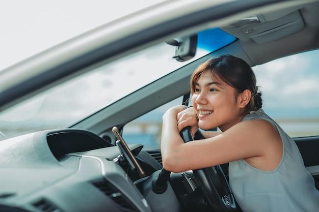 차를 운전하는 동안 웃고 똑바로 바라보는 매력적인 아시아 여성. 여행 휴가 편안하고 즐기는 개념.