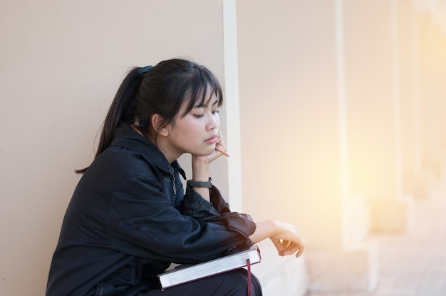 Attractive asian young girl sitting alone seem bored for reading book preparing exam