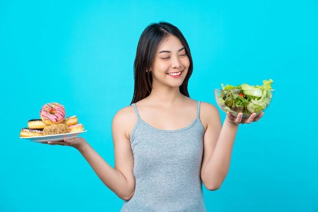 도넛 또는 야채 샐러드 디스크를 들고 선택하는 매력적인 아시아 젊은 여성