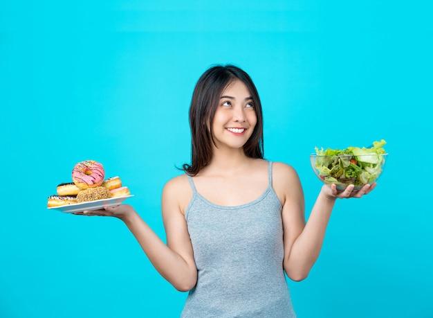 도넛 디스크를 들고 선택하는 매력적인 아시아 젊은 여성