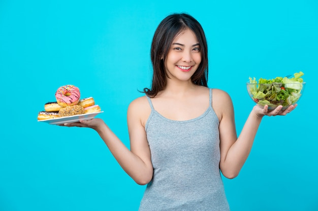 Attractive asian young woman holding and choosing between disk of donuts or vegetable salad in glasses bowl on isolated blue color wall