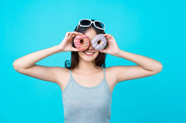 Attractive asian young woman playing with donuts on isolated blue color wall, weight loss and avoid junk food for dieting and healthy concept
