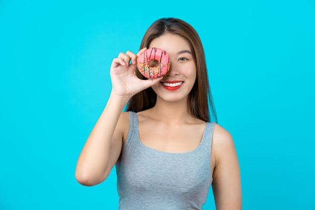 웃는 얼굴에 달콤한 도넛을 가지고 노는 매력적인 아시아 젊은 여성