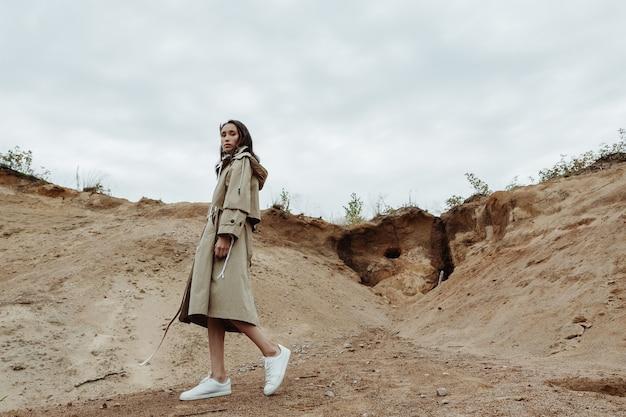 秋にベージュのスタイリッシュなトレンチコートで砂の採石場を歩いている魅力的なアジアの若い女性。