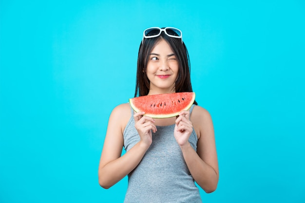 Привлекательная азиатская молодая женщина в летнем жилете и держит слайд арбуза