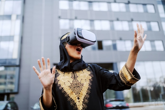 Attractive astonished young muslim woman in traditional wear standing in front of corporate building and using vr goggles.