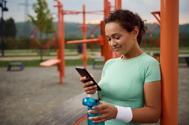 魅力的なアスリート混血美しい若い女性が水でボトルを保持し、スマートフォンでモバイルアプリケーションをチェックし、屋外でのスポーツ活動の後に休憩