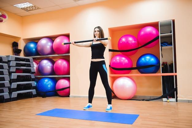 ジムで運動をしている魅力的なアスリート若い女性。