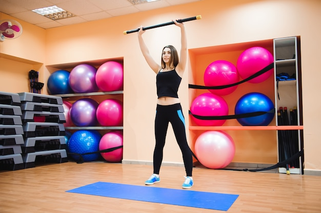 Attractive athlete young woman doing exercise at gym.