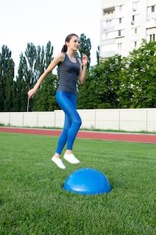 Привлекательная спортивная брюнетка женщина прыгает на мяч босу на стадионе