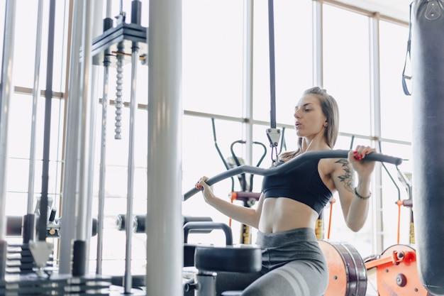 魅力的なスポーツ少女がシミュレータで肩を鍛えます。背中の筋肉の眺め。健康的な生活様式。