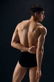 黒の背景に分離された黒のショートパンツの背面図で魅力的な運動選手
