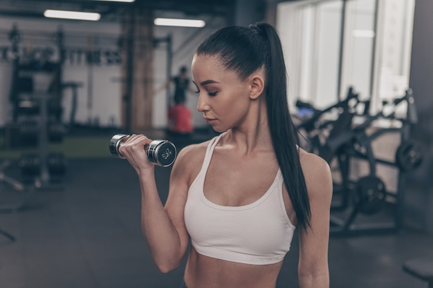 Attractive athletic young woman training with weights, copy space