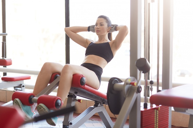 Attractive athltic woman pumps press on simulator in sports gym, tones muscles, liffting upper body, develop definition of muscles